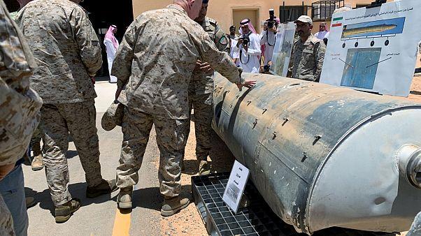 ضابط من التحالف الذي تقوده السعودية يعرض سلاحاً يقول التحالف إنه صناعة إيرانية على ضابط أميركي