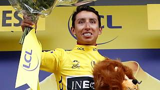 Team INEOS rider Egan Bernal of Colombia celebrates on the podium, wearing the overall leader's yellow jersey on July 26, 2019.