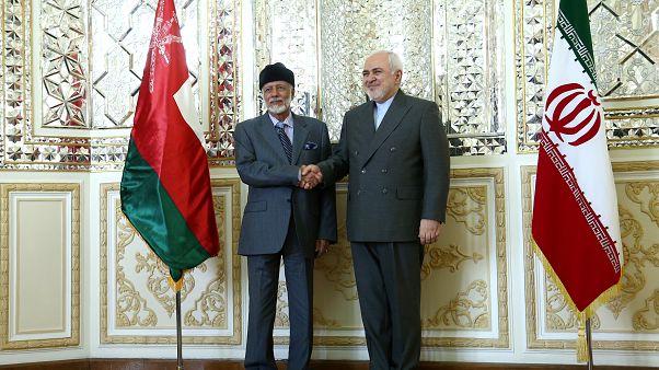 وزير الخارجية الإيراني محمد جواد ظريف (يمينا) يصافح الوزير العماني المسؤول عن الشؤون الخارجية يوسف بن علوي بن عبد الله في طهران يوم السبت