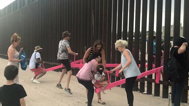 People play on a set of fluorescent pink seesaws across the US-Mexico border in Sunland Park, New Mexico, US