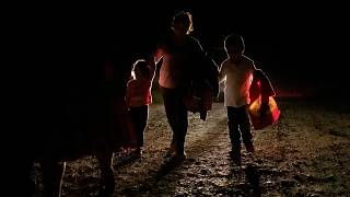 FILE PHOTO: A woman from Honduras and her two children are followed by a US Border Patrol vehicle after illegally crossing into the US from Mexico in Penitas, Texas