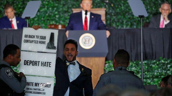 النائب في ولاية فرجينيا إبراهيم سميرة معترضاً على خطاب ترامب الذي يظهر في الخلفية