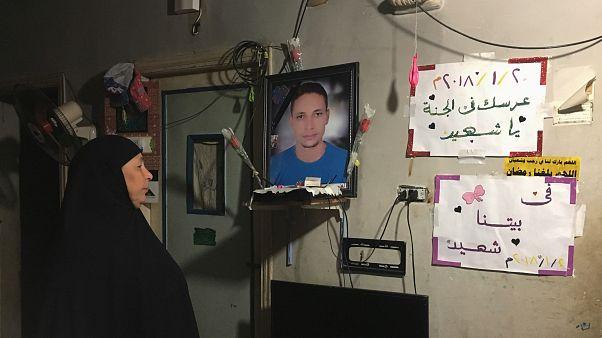 تهاني والدة الشاب لطفي إبراهيم تنظر إلى صورة له معلقة داخل منزل الأسرة في كفر الشيخ يوم 13 يناير كانون الثاني 2019
