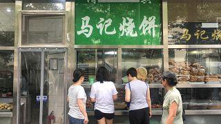 """كلمة """"حلال"""" المكتوبة باللغة العربية مغطاة على لافتة متجر في بكين 19 يوليو تموز 2019"""