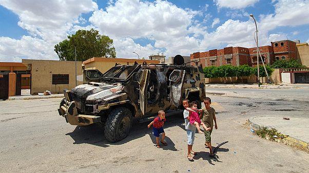 کودکان اهل لیبی در کنار یک خودروی نظامی