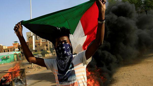 محتج ملثم يرفع علم السودان وخلفه إطارات تحترق أثناء احتجاج في العاصمة الخرطوم يوم 27 يوليو تموز 2019. تصوير: محمد نور الدين عبد الله
