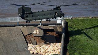 طائرة هليكوبتر عسكرية بريطانية تلقي أكياسا من الحصى على منحدر خارجي لسد انهار جزء منه وبات معرضا لخطر الانهيار وإغراق بلدة وايلي بريدج في منطقة ديربيشاير