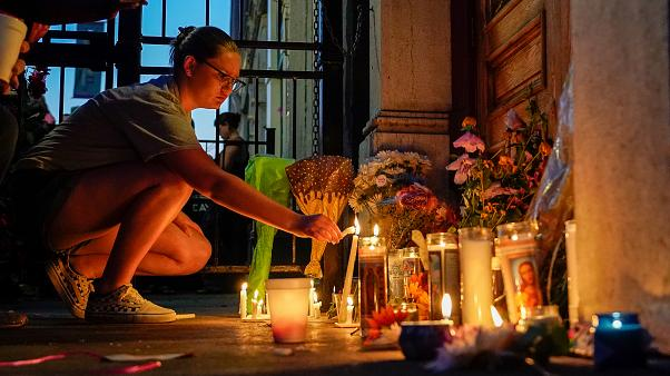 A mourner lights a candle at a memorial during a vigil at the scene of a mass shooting in Dayton, Ohio, U.S. August 4, 2019.