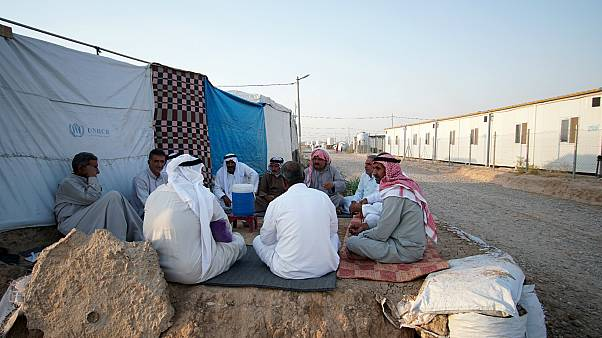 نازحون عراقيون آثروا العودة للمخيمات بعد أن وجدوا الظروف في مخيماتهم صعبة وبيوتهم مهدمة، يجلسون في خيام في شرق الموصل