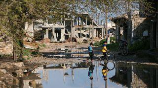 FILE PHOTO: Children play near damaged houses in Kobani, Syria