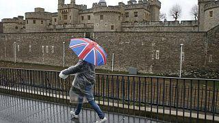 عابری با چتر منقش به پرچم بریتانیا از کنار برج لندن می گذرد