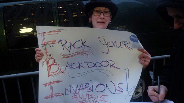 أميركية تحمل لافتة ضد قرصنة FBI على هواتف مواطنين أميركيين خلال وقفة احتجاجية أمام فرع أبل بالجادة الخامسة في نيويورك. شباط 2016