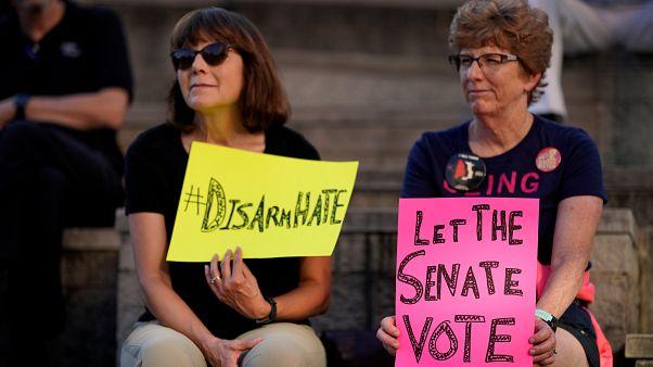 أمريكيتان تحملان لافتات تطالب بنزع الأسلحة