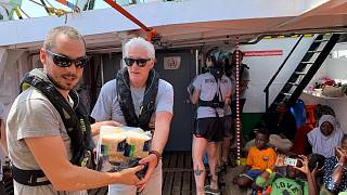 U.S. actor Richard Gere helps to carry supplies aboard the Open Arms rescue boat