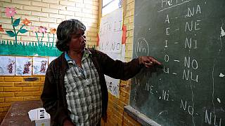 Professor Blas Duarte shows letters in the Maka language, in Mariano Roque Alonso, Paraguay