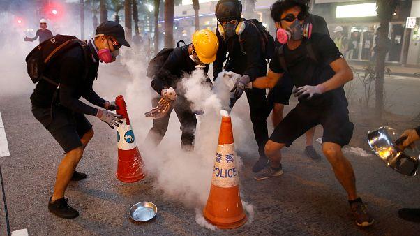 Des manifestants tentent d'éteindre des cartouches de gaz lacrymogène lors d'une manifestation dans le quartier de Wan Chai à Hong Kong