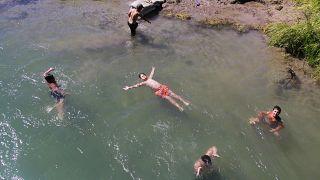 Tunceli'nin Ovacık ilçesinde çocuklar, Kurban Bayramı'nı, Munzur Çayı'nın serin sularında yüzerek geçiriyor.