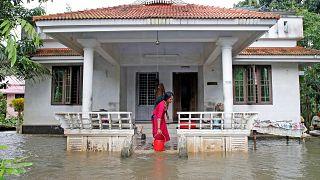 امرأة تزيح مياه الفيضانات عن منزلها في ولاية كيرالا جنوب الهند