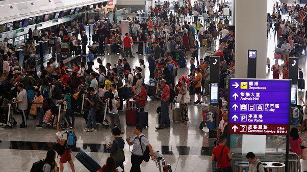 مسافرون يصطفون في مطار هونغ كونغ الدولي الذي أعيد افتتاحه بعد تعطل بسبب الاحتجاجات يوم الثلاثاء
