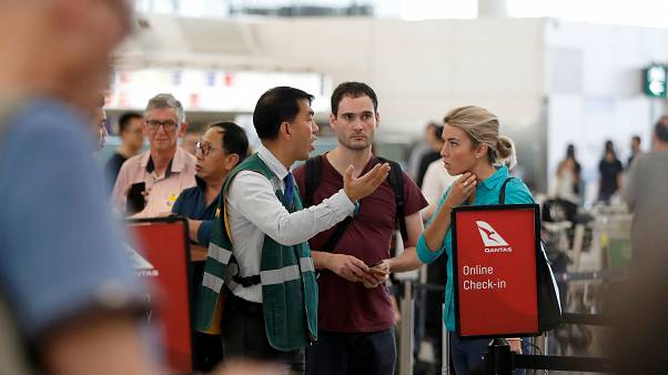 مسافرون يتحدثون مع أحد موظفي مطار هونغ كونغ يوم الثلاثاء