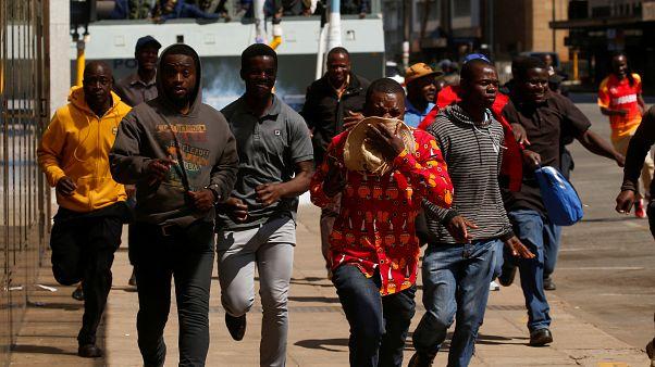 محتجون يفرون من غاز مسيل للدموع أطلقته شرطة زيمبابوي