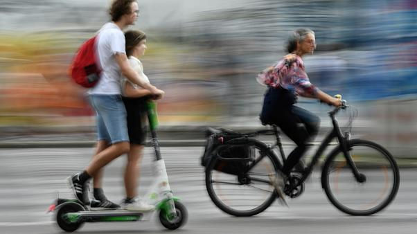 Radfahrerin überholt in Berlin zwei Verkehrsteilnehmer auf einem E-Tretroller.