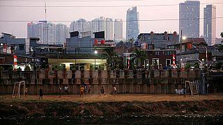 Una partitella di pallone tra ragazzi e, dietro, lo skyline di Giacarta.