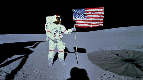 رائد الفضاء آلان  شيبارد، قائد مهمة الهبوط على سطح القمر أبولو 14، إلى جانب علم الولايات المتحدة على سطح القمر
