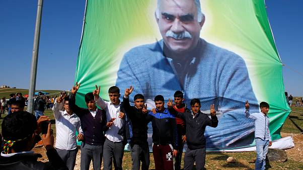 Kurdish men pose for a picture in front of the portrait of jailed Kurdish militant leader Abdullah Ocalan