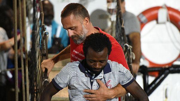 Un migrant aidé à descendre du navire humanitaire Open Arms
