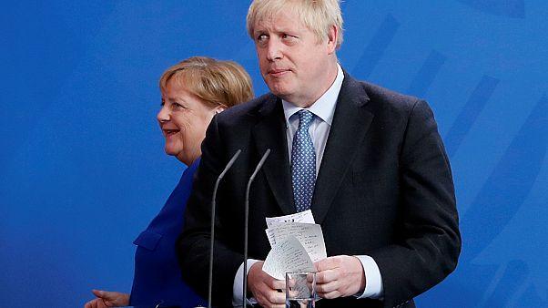 El Primer Ministro de Gran Bretaña, Boris Johnson, sostiene sus notas mientras asiste a una conferencia de prensa con la Canciller alemana Angela Merkel.
