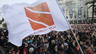 People hold flags with logo of Rustavi 2, Georgia's biggest independent television station, during rally..