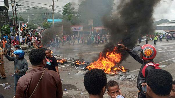 أشخاص يحرقون الإطارات أثناء احتجاج على طريق في مانوكواري ، بابوا الغربية- أرشيف رويترز