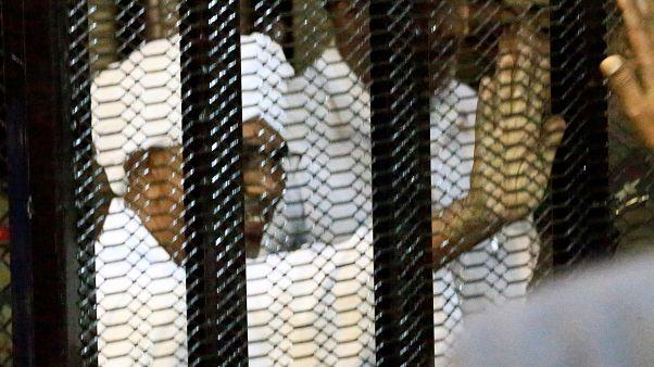 البشير ملوحاً لأنصاره من وراء قضبان السجن (في المحكمة)