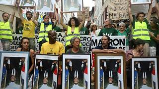 Climate activists rally carrying stolen portraits of Macron near G7