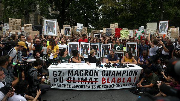 """Manifestantes mostram cartaz com a frase: """"Macron campeão do 'blá blá blá"""""""