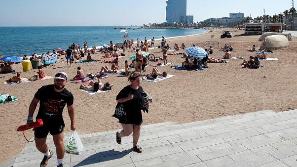 Die Leute verlassen den Strand von Sant Sebastia, nachdem die Polizei einen Sprengsatz im Wasser gefunden und einen Teil davon evakuiert hat