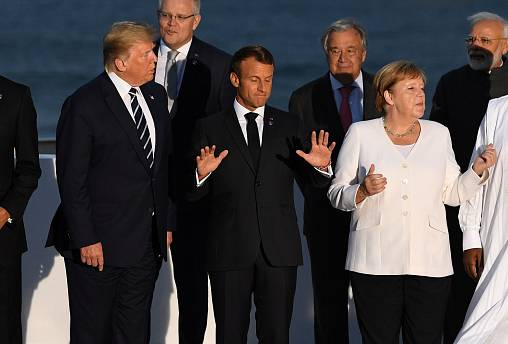 French President Emmanuel Macron, U.S. President Donald Trump and German Chancellor Angela Merkel pose for a family photo with invited guests during the G7 summit in Biarritz,