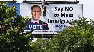 عامل يزيل لوحة إعلانات كبيرة مناهضة للهجرة عليها صورة لماكسيم بارنيه زعيم الحزب الشعبي الكندي اليميني في تورونتو