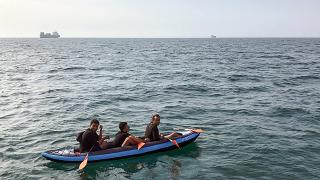 Three migrants who were attempting to cross The English Channel from France to Britain are seen as they drift in an inflatable canoe off the French coast at Calais on August 4
