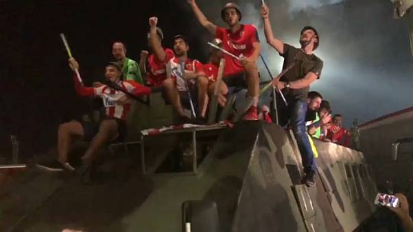 Red Star Belgrade players ride on military vehicle to celebrate win
