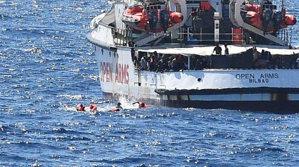 igrants jump off the Spanish rescue ship Open Arms, close to the Italian shore in Lampedusa