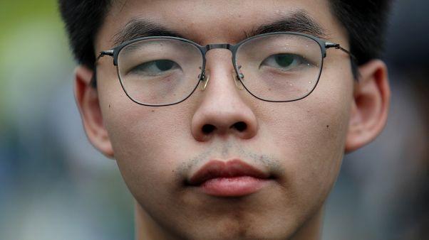 الناشط المؤيد للديمقراطية جوشوا وونغ ينظر إلى خارج المجلس التشريعي خلال مظاهرة تطالب قادة هونغ كونغ بالتنحي وسحب قانون تسليم المجرمين، في هونغ كونغ، الصين