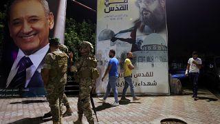 جنود لبنانيون بالقرب من ملصق عليه صورة أمين عام حزب الله، حسن نصر الله، على الحدود الجنوبية اللبنانية