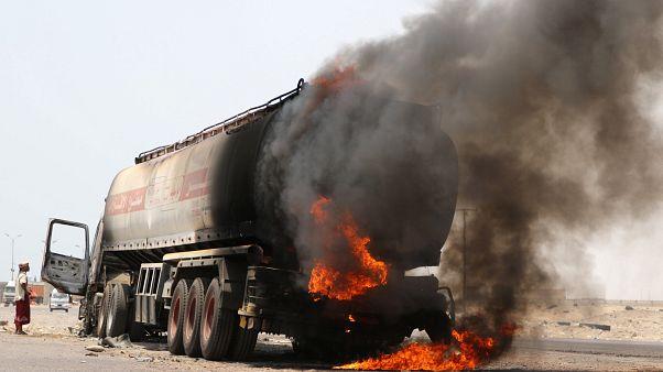 رجل يقف بجانب شاحنة صهريج نفط اشتعلت فيها النيران خلال اشتباكات بين الانفصاليين والقوات الحكومية بالقرب من عدن