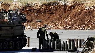 جنود إسرائيليون يقفون بجانب القذائف ووحدة مدفعية متحركة بالقرب من الجانب الإسرائيلي من الحدود مع سوريا- أرشيف رويترز