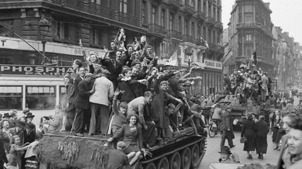 Belgian civilians cheer British troops in Brussels on September 4, 1944.