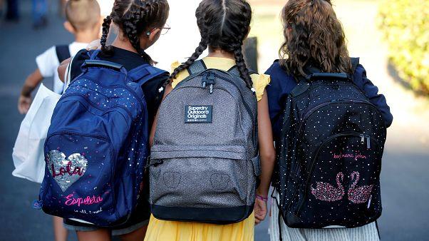 ثلاث تلميذات بانتظار الحافلة في مدينة مارسيليا الفرنسية للالتحاق بأول يوم مدرسي