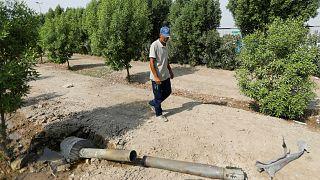 رجل ينظر إلى قذيفة في حديقته قرب بغداد- أرشيف رويترز