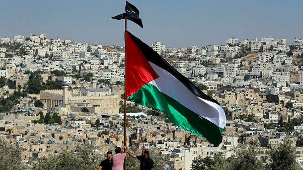 متظاهرون يرفعون العلم الفلسطيني خلال احتجاج على الزيارة المزمعة لرئيس الوزراء الإسرائيلي نتنياهو إلى مدينة الخليل في الضفة الغربية